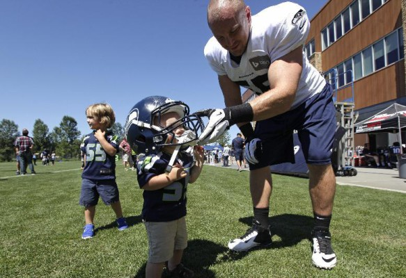 Seattle Seahawks' Heath Farwell, right, leans down as he helps his son Beau, 1, try on his helmet as other son Brock, 3 (AP Photo Elaine Thompson)
