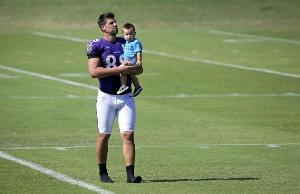 Baltimore Ravens tight end Dennis Pitta carries his son Decker on the field after an NFL football training camp practice on Saturday, July 26, 2014, in Owings Mills, Md (AP Photo Patrick Semansky)