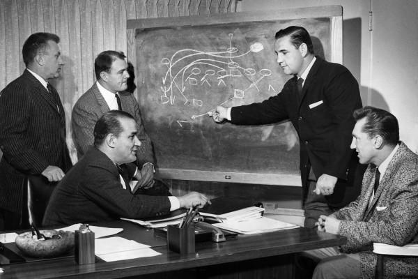 March, 1960: Los Angeles Chargers coaching staff moved into new offices at 1017 La Brea. Here assistant Jack Faulkner diagrams play for Joe Madro, left, Chuck Noll; head coach Sid Gillman (seated) and Al Davis. In 1959, Madra, Faulkner and Gillman were with the Los Angeles Rams; Noll with Cleveland Browns and Davis with USC. This photo was published in the March 15, 1960 Los Angeles Times.