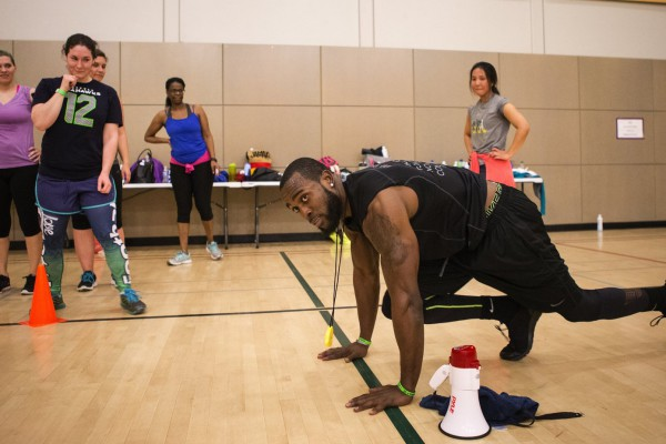 "Marissa Scroggins, in a ""12"" shirt, watches as Kam Chancellor demos mountain climber exercises during a Form by Force Women's Boot Camp at the Gymnasium at Les Gove Park in Auburn on Wednesday, March 30, 2016. The Seahawks safety hosts the workouts, along with Kevin Allen, his personal trainer and co-owner of Form by Force. ""Special guests,"" like teammate Richard Sherman, sometimes make appearances."